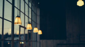 Lamper som henger ned fra taket i et mørkt rom som gir en dempet belysning.