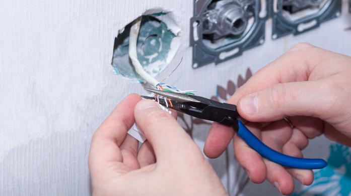 hendene til en elektriker som installerer en stikkontakt.