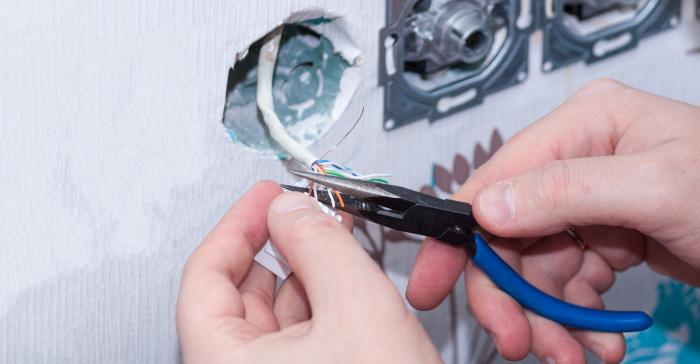 Hender til en elektriker som installerer stikkontakt, nærbilde.
