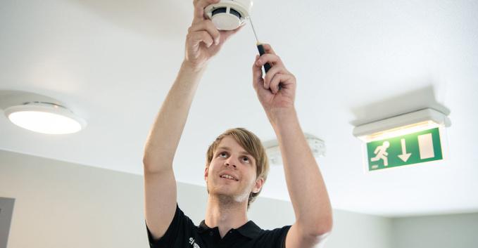 En elektriker som skifter batteriet i en brannvasler