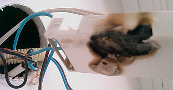 En stikkontakt som har tatt fyr på grunn av varmegang
